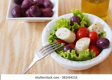 Fresh salad of heart of palm (palmito), cherry tomatos and olives on white plate. Selective focus