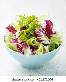 Fresh salad leaves mix in blue bowl