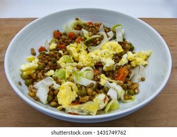 Fresh salad with lentils, carots, peas and scrambled eggs