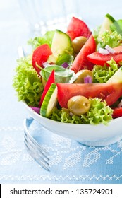 Fresh salad with lettuce, tomato, cucumber and olives