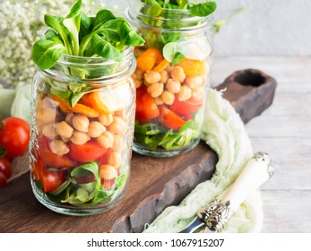 Fresh salad lunch with chickpeas, tomatoes, carrots and valerian served in mason jars