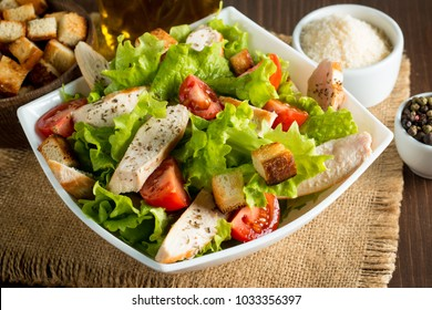Fresh salad made of tomato, ruccola, chicken breast, arugula, crackers and spices. Caesar salad in a white, transparent bowl on wooden background