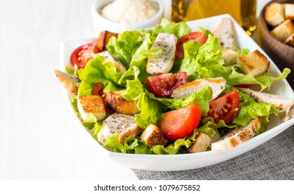 Fresh salad made of tomato, ruccola, chicken breast, arugula, eggs, crackers and spices. Caesar salad in a white, transparent bowl on wooden background