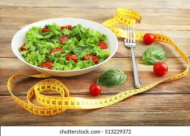 Fresh salad and measuring tape on wooden  background