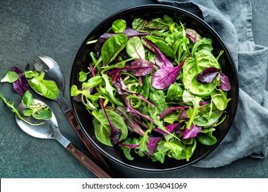 Fresh salad mix of baby spinach, arugula leaves, basil, chard and lambs lettuce. Salad bowl, healthy food, top view