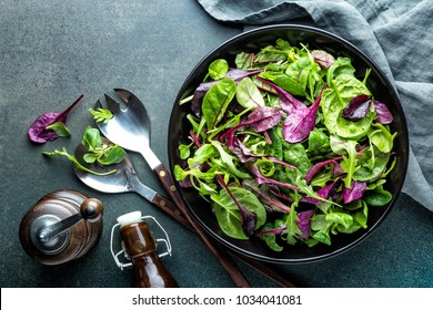 Fresh salad mix of baby spinach, arugula leaves, basil, chard and lambs lettuce. Salad bowl, healthy food, top view