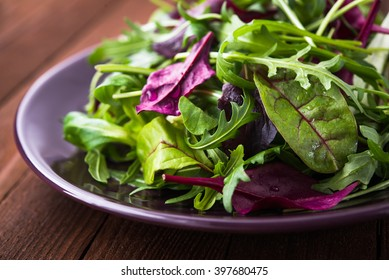 Fresh salad with mixed greens (arugula, mesclun, mache) on dark wooden background close up. Healthy food.