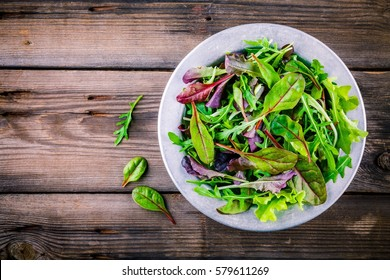Fresh salad with mixed greens in bowl on wooden background