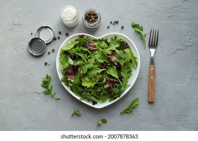 Fresh salad mixture of arugula leaves, mizuna lettuce, peas and lollo rosso in a heart-shaped plate, salt and spices on a gray concrete background. Concept: healthy food, top view.