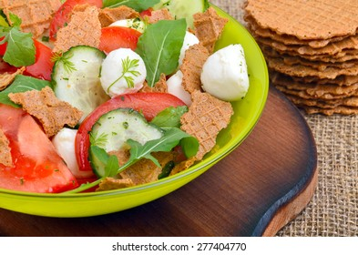 Fresh salad mozzarella with wafers, tomatoes, cucumber and arugula leaves on the desk