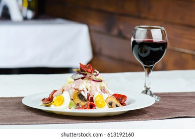 Fresh Salad With Mushrooms, Grilled Vegetables, Boiled Eggs, White Cheese, Olive And Ham With Glass Of Red Wine On Wooden Background