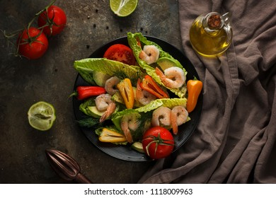 Fresh salad with olive oil, shrimps, peppers, limes and tomatoes. Home made food. Concept for a tasty and healthy meal. Dark stone background. Top view. Close up.