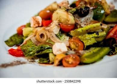 Fresh salad on the white plate. Restaurant