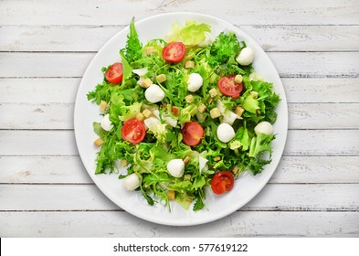 Fresh salad on white plate on wooden planks.