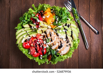 Fresh salad plate with colorful tomatoes, chicken, cheese, avocado, lime, balsamic mousse and mixed greens on wooden background top view. Healthy food. Nutritious meal.