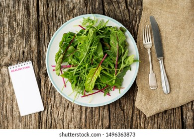 Fresh salad plate with mixed greens (arugula, mesclun, mache) on dark wooden background with cutlery and notepad. Healthy food. Green meal. Flat lay