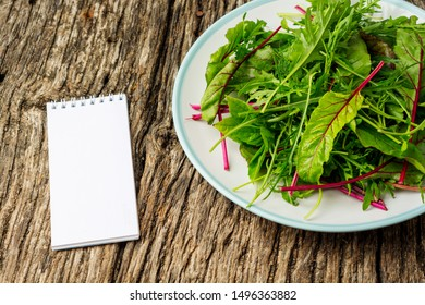 Fresh salad plate with mixed greens (arugula, mesclun, mache) on dark wooden background with notepad close up. Healthy food. Green meal. Flat lay
