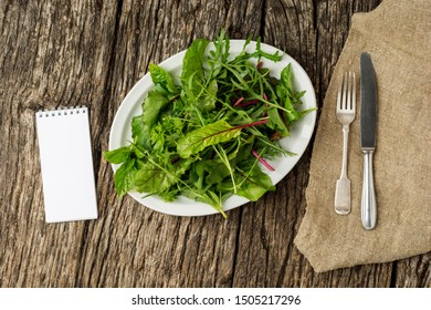 Fresh salad plate with mixed greens (arugula, mesclun, mache) on dark wooden background with cutlery and notepad. Healthy food. Green meal. Flat lay.