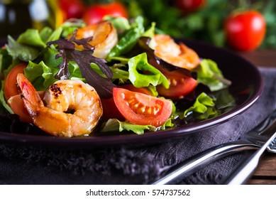 Frische Salatplatte mit Garnelen, Tomaten und gemischten Grünen (Arugula, mesclun, mache) auf Holzhintergrund, Nahaufnahme. Gesundes Essen. Sauberes Essen.