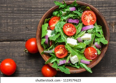 Fresh salad with rucola, tomatoes cherry, feta cheese and red onion in a bowl on rustic wooden table. top view with copy space