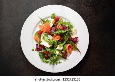 Fresh salad with salmon and cheese on white plate