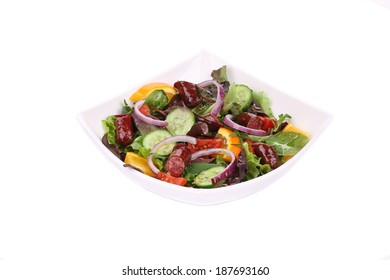Fresh salad with sausage. Isolated on a white background.