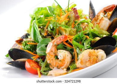 Fresh salad with seafood on white plate