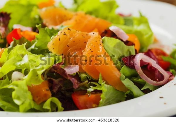 Fresh salad with smoked salmon. Vintage scenery.