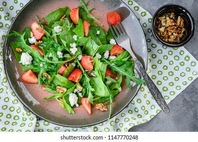 Fresh salad with spinach, avocado, strawberries, arugula and cheese, top view.