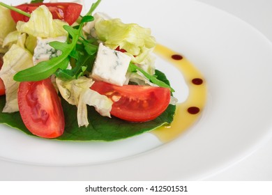 Fresh salad with spinach, cherry tomatoes, blue cheese and arugula. Close up image.