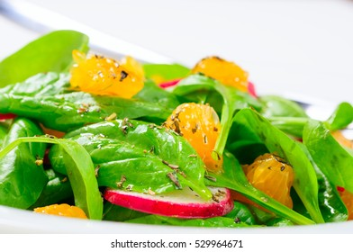 fresh salad with spinach, radish and orange.