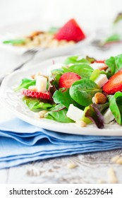 Fresh salad with strawberries, spinach leaves and feta cheese on white wooden background, selective focus