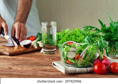 Fresh salad of summer vegetables in a deep bowl of glass. Arugula, lettuce, radishes, onions, cherry tomatoes. In the background male hand sliced onions on cutting board. healthy lifestyle. copy space