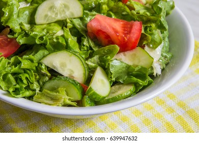 Fresh salad. Tomato, cucumber and greens in white bowl.