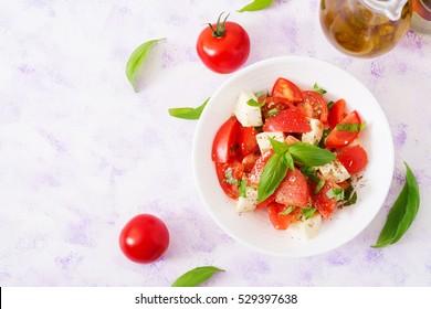Fresh salad with tomato, mozzarella and basil. Top view.