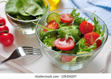 fresh salad with tomatoes cherry, arugula and cucumber in glass bowl
