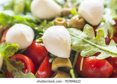 Fresh salad with tomatoes, green olives and mozzarella in glass bowl on marble table. Selective focus, close up