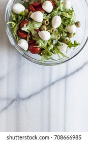 Fresh salad with tomatoes, green olives and mozzarella in glass bowl on marble table. Selective focus