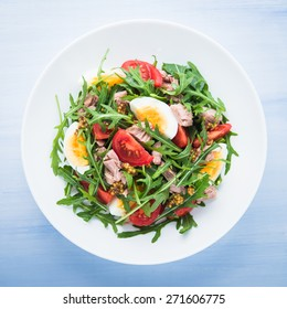 Fresh salad with tuna, tomatoes, eggs, arugula and mustard on blue wooden background top view. Healthy food.
