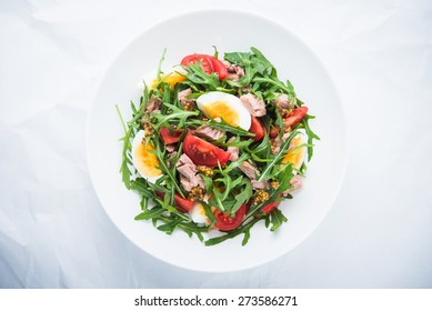 Fresh salad with tuna, tomatoes, eggs, arugula and mustard on white textured background top view. Healthy food.