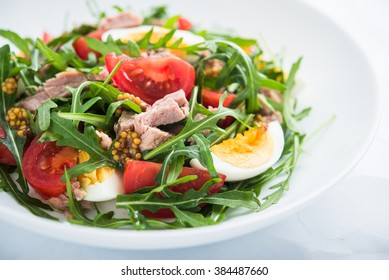Fresh salad with tuna, tomatoes, eggs, arugula and mustard on white textured background close up. Healthy food.