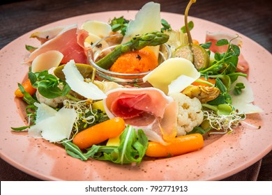 Fresh salad from vegetables, cheese and ham, on a colored plate