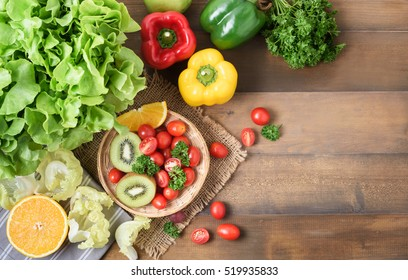 Fresh salad vegetables and fruit, tomato bell pepper, parsley, kiwi fruit on wood background, concept diet and healthy food.