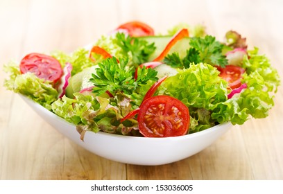 fresh salad with vegetables and greens on wooden table