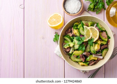 Fresh salad with vegetables and tuna in bowl on wooden background. Top view. Copy space.