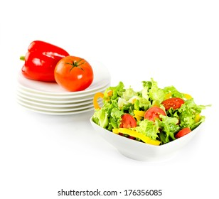 Fresh salad and vegetables in white plates isolated on white with clipping path