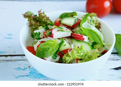 Fresh salad in a white bowl, food closeup