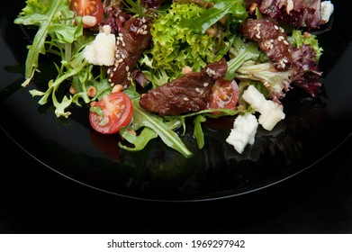 Fresh salat with meat, tomatoes, salat on the black plate. Vegan food. - Shutterstock ID 1969297942