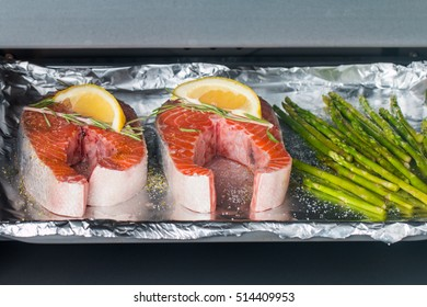 fresh salmon with asparagus in foil paper, ready for cooking in oven
