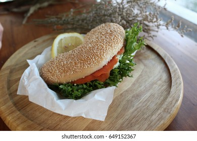 Fresh Salmon burgers with green vegetables on wooden plate. Food decoration.